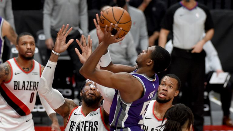Sacramento Kings guard De'Aaron Fox drives to the basket on Portland Trail Blazers forward Robert Covington and guard Rodney Hood