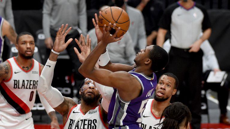 Sacramento Kings guard De'Aaron Fox drives to the basket on Portland Trail Blazers forward Robert Covington and guard Rodney Hood
