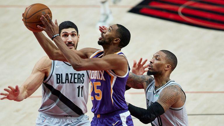 Phoenix Suns striker Mikal Bridges shoots between Portland Trail Blazers center Enes Kanter and guard Damian Lillard