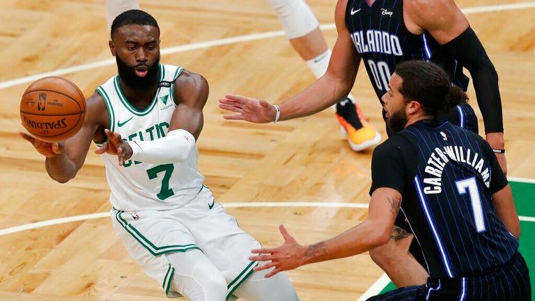 AP - Boston Celtics' Jaylen Brown, left, passes off against Orlando Magic's Michael Carter-Williams