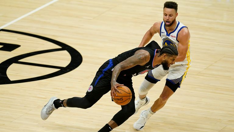 Los Angeles Clippers guard Paul George dribbles past Golden State Warriors keeper Stephen Curry