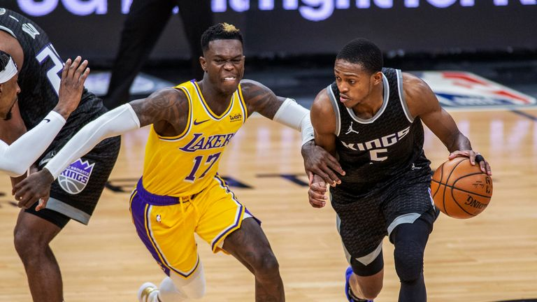 Sacramento Kings guard De'Aaron Fox drives to the basket as he's defended by Los Angeles Lakers guard Dennis Schroder