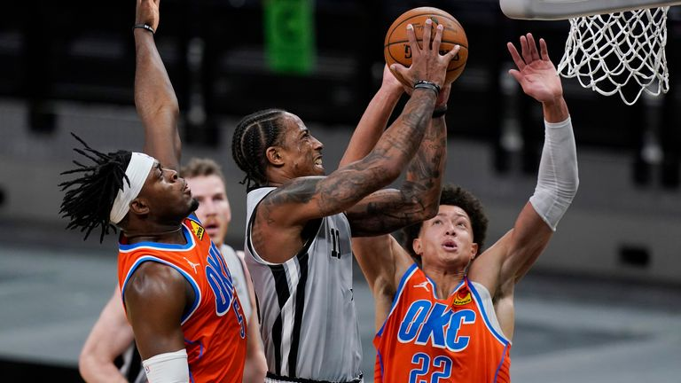 San Antonio Spurs forward DeMar DeRozan drives to the basket between Oklahoma City Thunder forward Luguentz Dort and center Isaiah Roby