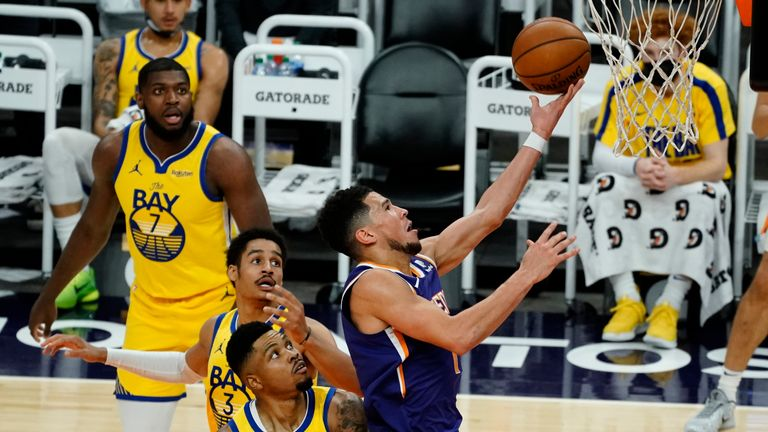 Phoenix Suns guard Devin Booker drives past Golden State Warriors guard Jordan Poole and forward Kent Bazemore