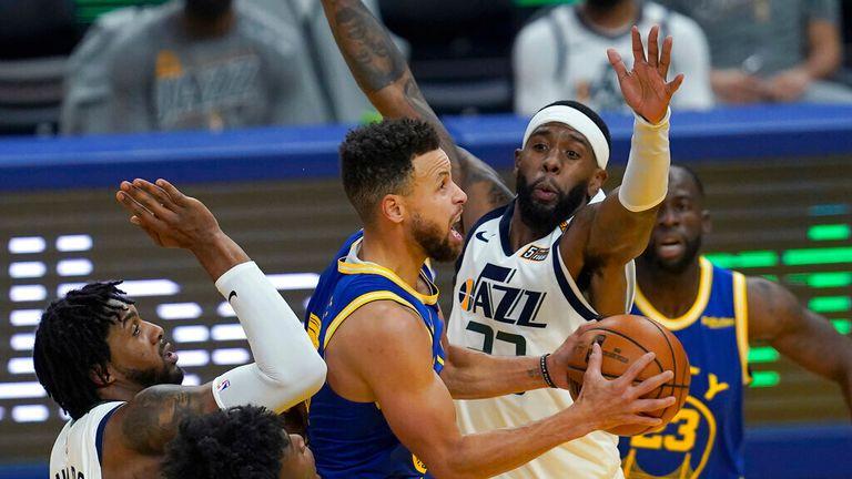AP - Golden State Warriors guard Stephen Curry, center, shoots between Utah Jazz center Derrick Favors, left, and forward Royce O'Neale