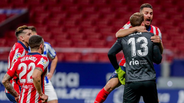 Jan Oblak is mobbed after his late penalty save for Atletico Madrid
