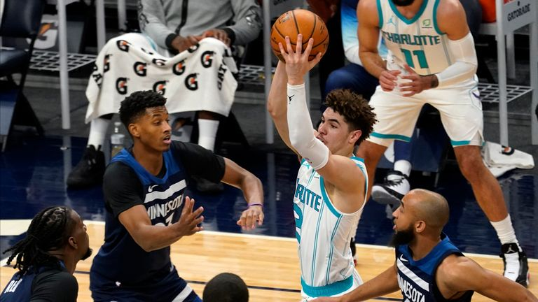 Charlotte Hornets' LaMelo Ball looks to pass as Minnesota Timberwolves' Jarrett Culver and Jordan McLaughlin defend
