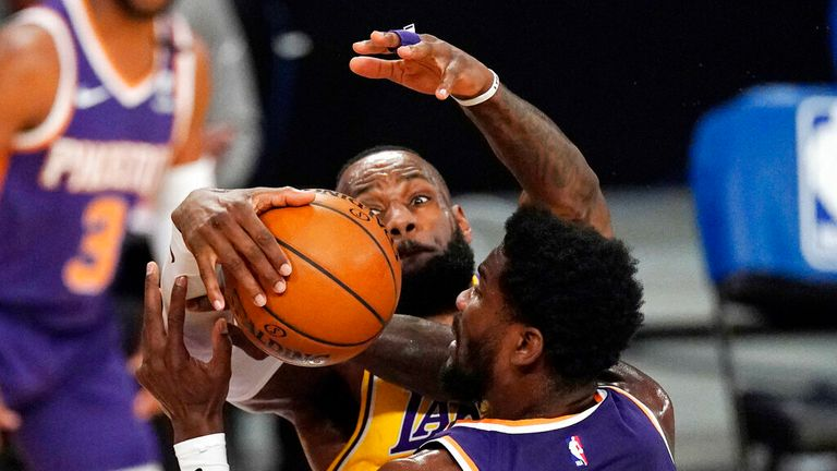 AP - Los Angeles Lakers forward LeBron James, left, blocks the shot of Phoenix Suns center Deandre Ayton