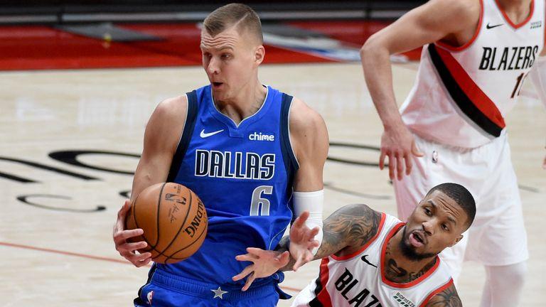 Portland Trail Blazers guard Damian Lillard, reaches for the ball held by Dallas Mavericks center Kristaps Porzingis