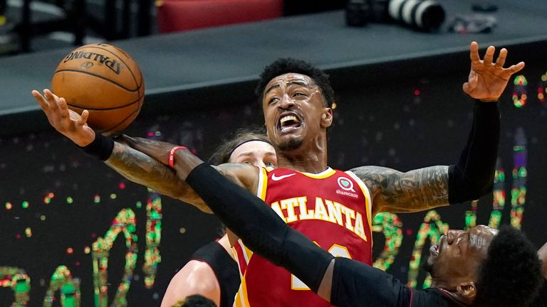 Atlanta Hawks forward John Collins, center top, is fouled by Miami Heat center Bam Adebayo, right, during the second half of an NBA basketball game, Sunday, Feb. 28, 2021, in Miami.