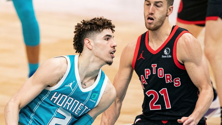 Charlotte Hornets guard LaMelo Ball (2) drives to the basket while guarded by Toronto Raptors guard Matt Thomas (21) during the second half of an NBA basketball game in Charlotte, N.C., Saturday, March 13, 2021.