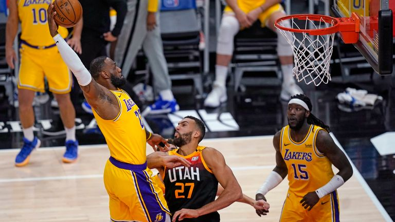 Los Angeles Lakers forward LeBron James, left, goes to the basket as Utah Jazz center Rudy Gobert (27) defends during the first half of an NBA basketball game Wednesday, Feb. 24, 2021, in Salt Lake City.