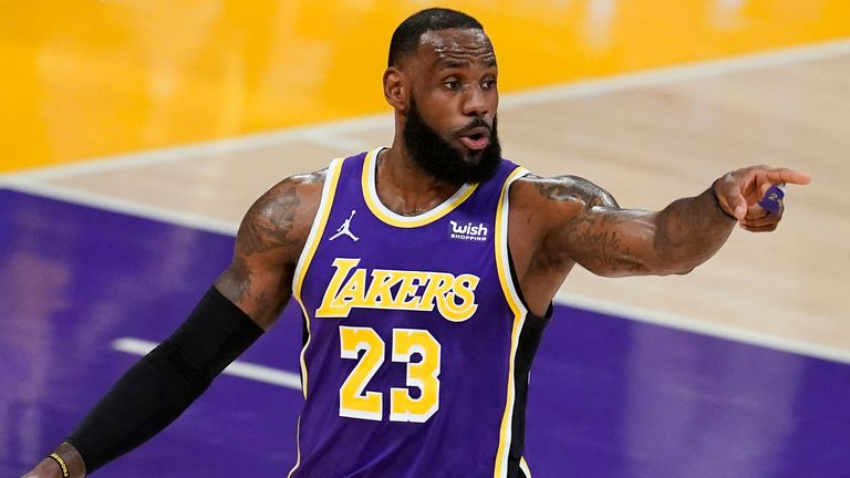 Los Angeles Lakers forward LeBron James signals to a teammate during the first half of an NBA basketball game against the Charlotte Hornets on Thursday, March 18, 2021, in Los Angeles. (