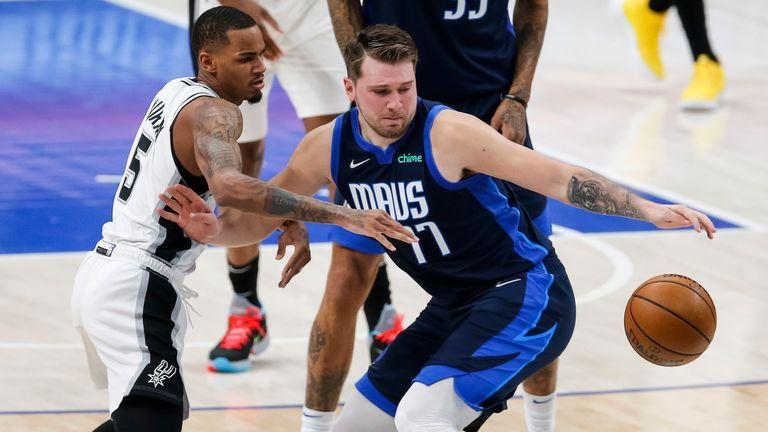 Dallas Mavericks guard Luka Doncic (77) reaches for the ball, while fending off San Antonio Spurs guard Dejounte Murray (5) during the first half of an NBA basketball game Wednesday, March 10, 2021, in Dallas. (AP Photo/Brandon Wade)