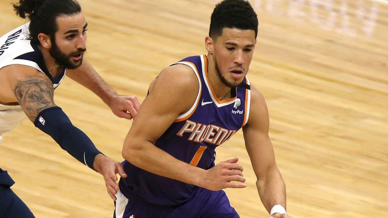 Phoenix Suns' Devin Booker (1) drives the ball past Minnesota Timberwolves' Ricky Rubio (9) in the first half of an NBA basketball game, Sunday, Feb. 28, 2021, in Minneapolis.