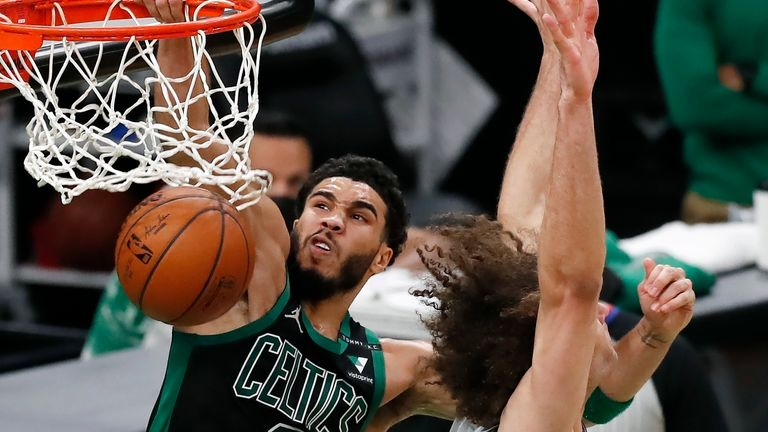 Boston Celtics' Jayson Tatum (0) dunks against Washington Wizards' Robin Lopez (15) during the first half of an NBA basketball game, Sunday, Feb. 28, 2021, in Boston.