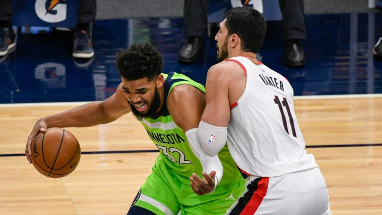 Minnesota Timberwolves center Karl-Anthony Towns (32) drives past Portland Trail Blazers center Enes Kanter (11) during the first half of an NBA basketball game Saturday, March 13, 2021, in Minneapolis.