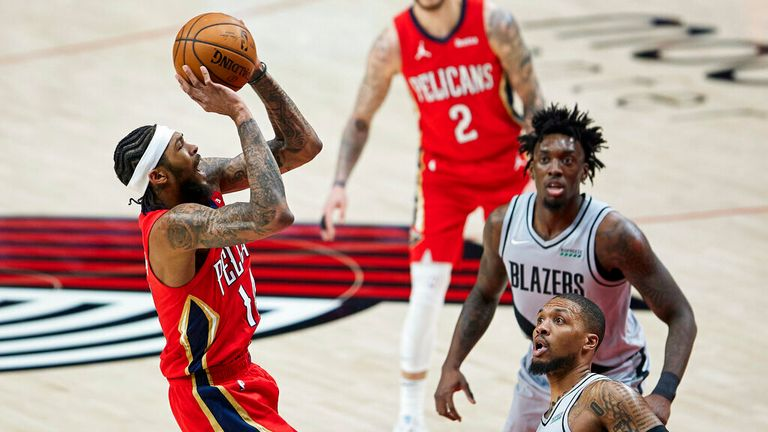 AP - New Orleans Pelicans forward Brandon Ingram, left, shoots over Portland Trail Blazers guard Damian Lillard