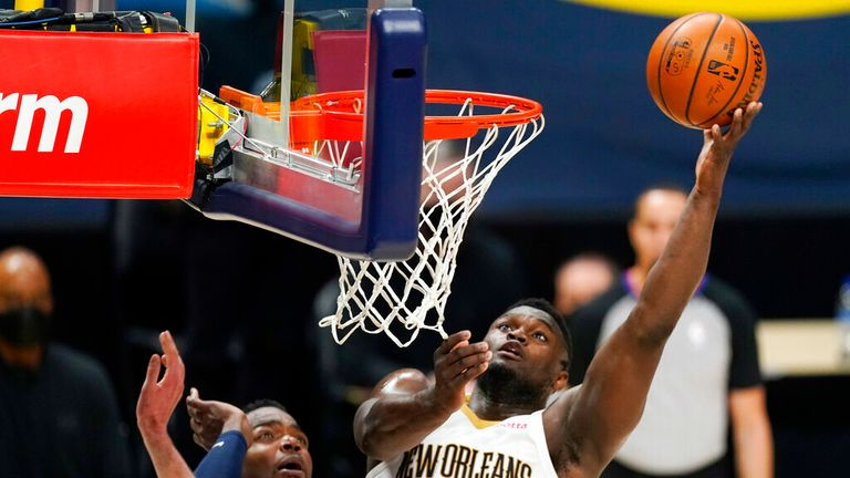 AP- New Orleans Pelicans forward Zion Williamson, right, drives to the rim as Denver Nuggets center Nikola Jokic defends