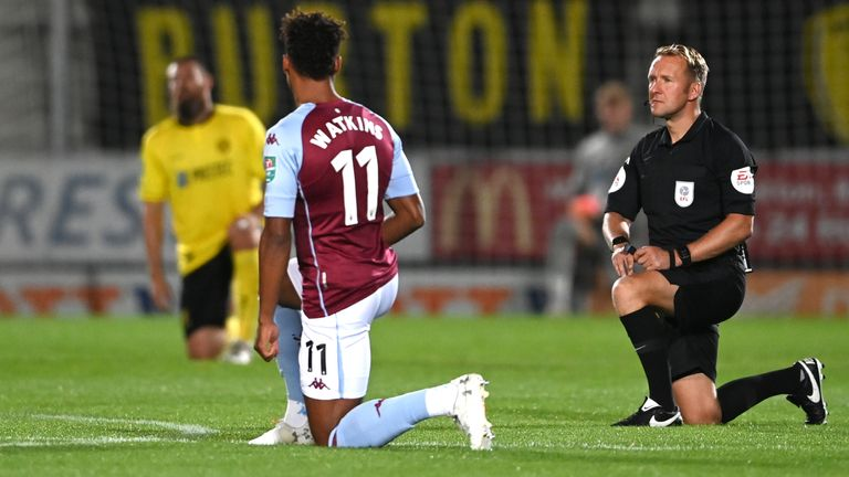 Aston Villa's Ollie Watkins and match referee Oliver Langford take a knee in support of the Black Lives Matter movement before the Carabao Cup match at the Pirelli Stadium, Burton.