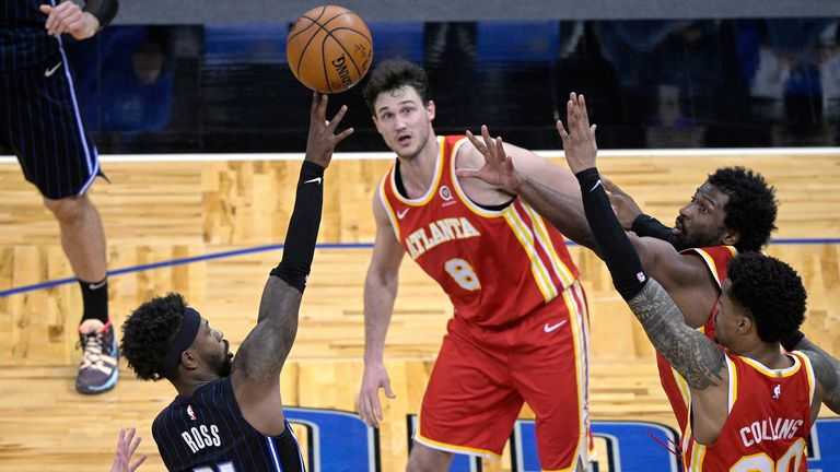 Orlando Magic guard Terrence Ross shoots in the final seconds as Atlanta Hawks' Kevin Huerter, Danilo Gallinari, Solomon Hill and John Collins defend