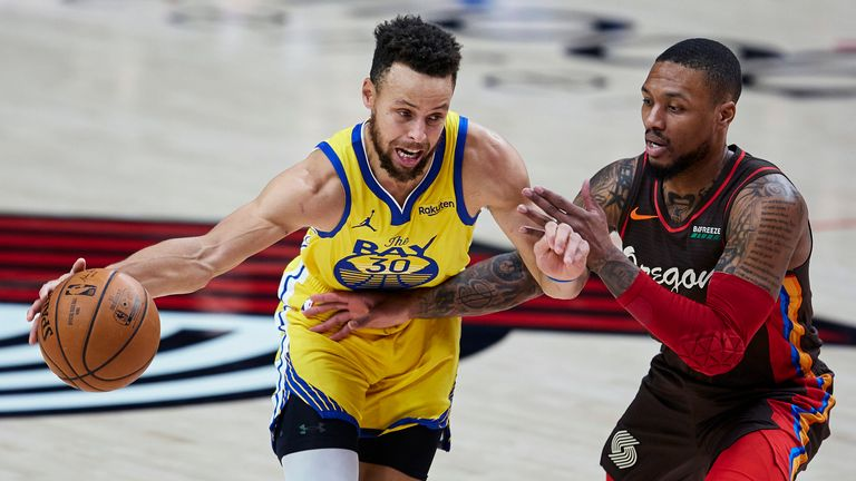 Golden State Warriors guard Stephen Curry dribbles past Portland Trail Blazers guard Damian Lillard