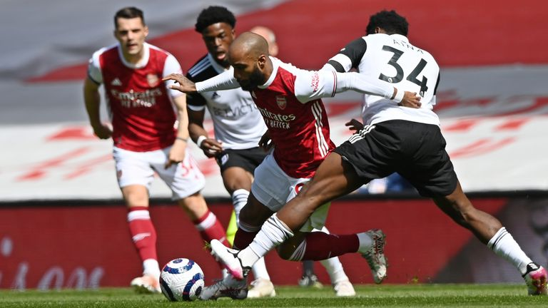 Arsenal's Alexandre Lacazette, centre, tries to get past Fulham's Ola Aina, right, during an English Premier League soccer match between Arsenal and Fulham at the Emirates stadium