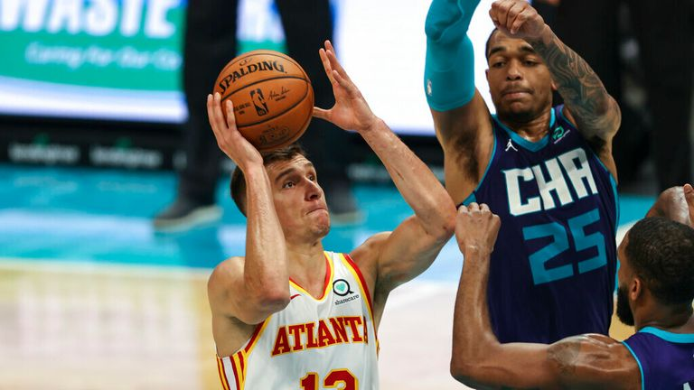 AP - Atlanta Hawks guard Bogdan Bogdanovic, left, shoots over Charlotte Hornets forward P.J. Washington, center, and guard Brad Wanamaker