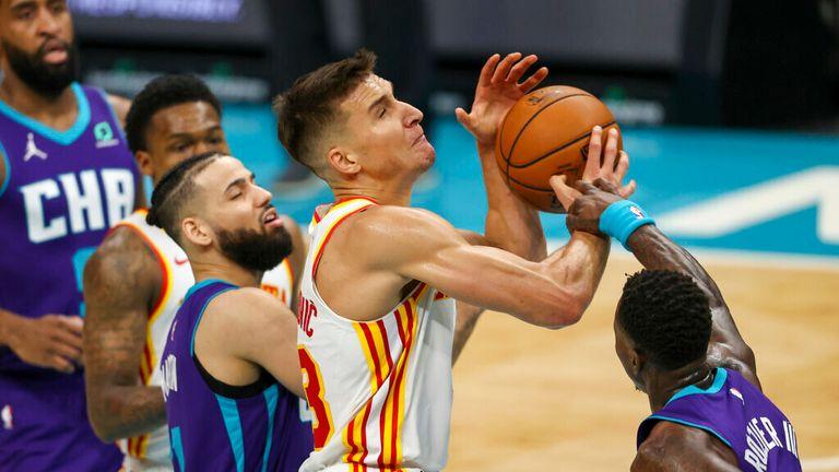 AP - Atlanta Hawks guard Bogdan Bogdanovic, center, drives to the basket against Charlotte Hornets guard Terry Rozier