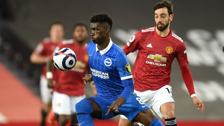Brighton's Yves Bissouma, left, and Manchester United's Bruno Fernandes challenge for the ball during the English Premier League soccer match between Manchester United and Brighton and Hove Albion at Old Trafford, Manchester, England, Sunday, Apr. 4, 2021. (Oli Scarff/Pool via AP)
