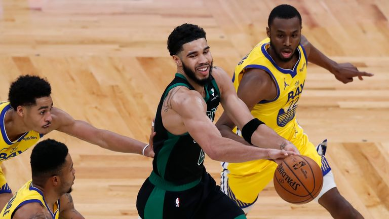 Boston Celtics' Jayson Tatum, center, passes off against Golden State Warriors' Jordan Poole, left, Kent Bazemore, second from left, and Andrew Wiggins (22) during the second half of an NBA basketball game, Saturday, April 17, 2021, in Boston. (AP Photo/Michael Dwyer)