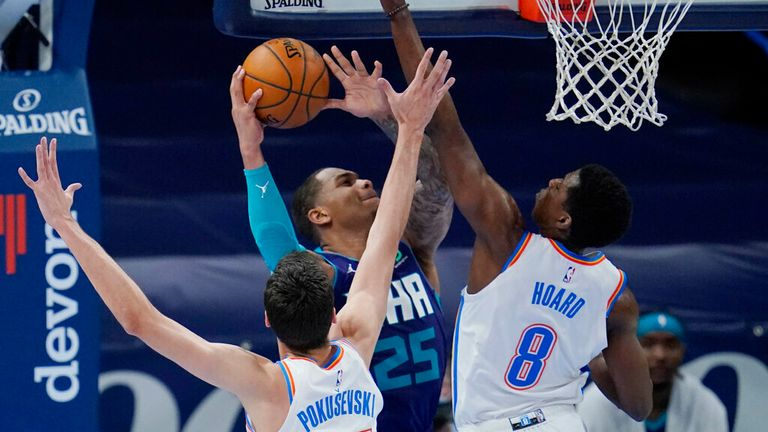 AP - Charlotte Hornets forward P.J. Washington (25) goes to the basket defended by Oklahoma City Thunder forward Aleksej Pokusevski