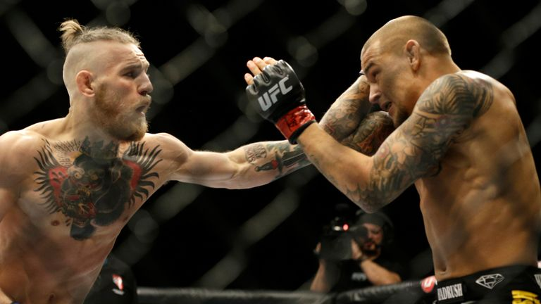 Sept. 27, 2014, file photo, Conor McGregor, left, and Dustin Poirier, exchange hits during their mixed martial arts bout in Las Vegas.