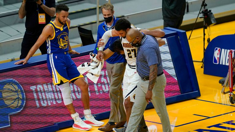 AP - Golden State Warriors' Stephen Curry, left, watches as Denver Nuggets guard Jamal Murray (27) is helped off the floor