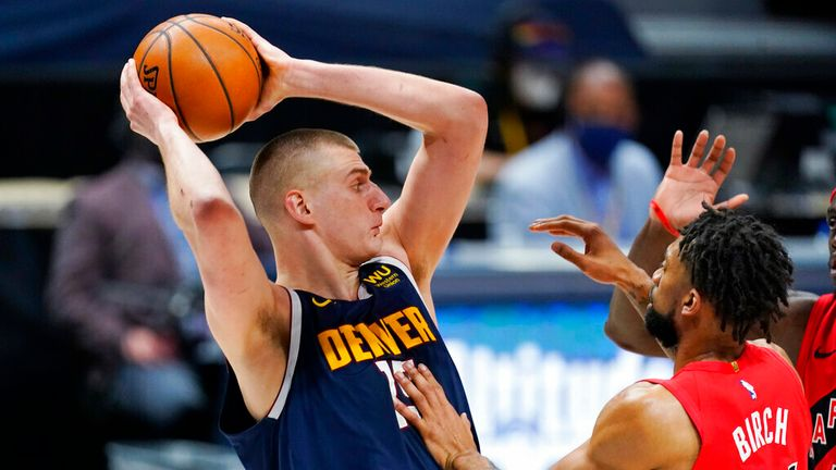 AP - Denver Nuggets center Nikola Jokic, left, pulls in a rebound as center Khem Birch defends