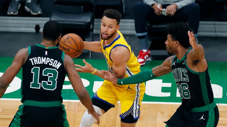 Boston Celtics' Tristan Thompson (13) and Marcus Smart (36) defend against Golden State Warriors' Stephen Curry during the second half of an NBA basketball game, Saturday, April 17, 2021, in Boston. (AP Photo/Michael Dwyer)