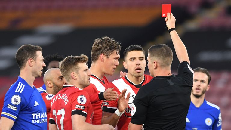 Referee Robert Jones shows a red card to Southampton's Jannik Vestergaard for his challenge on Leicester's Jamie Vardy