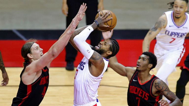 AP - Los Angeles Clippers' Paul George looks to shoot against Houston Rockets' Kelly Olynyk (41) and Armoni Brooks