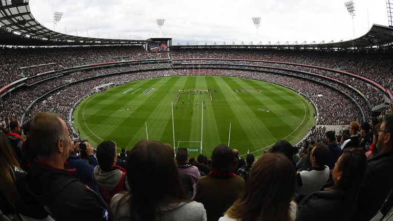 The MCG crowd stands for the Last Post ahead of the AFL match between the Collingwood Magpies and the Essendon Bombers
