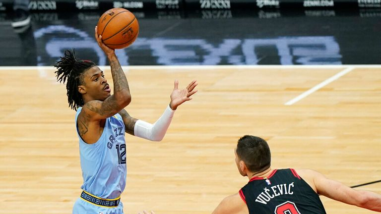 AP - Memphis Grizzlies guard Ja Morant, left, shoots as Chicago Bulls center Nikola Vucevic defends