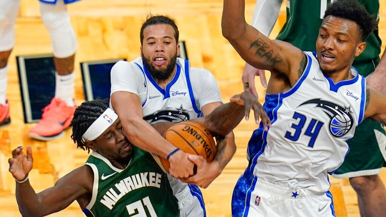 AP - Milwaukee Bucks guard Jrue Holiday (21) goes after a rebound against Orlando Magic guard Michael Carter-Williams, center, and center Wendell Carter Jr.