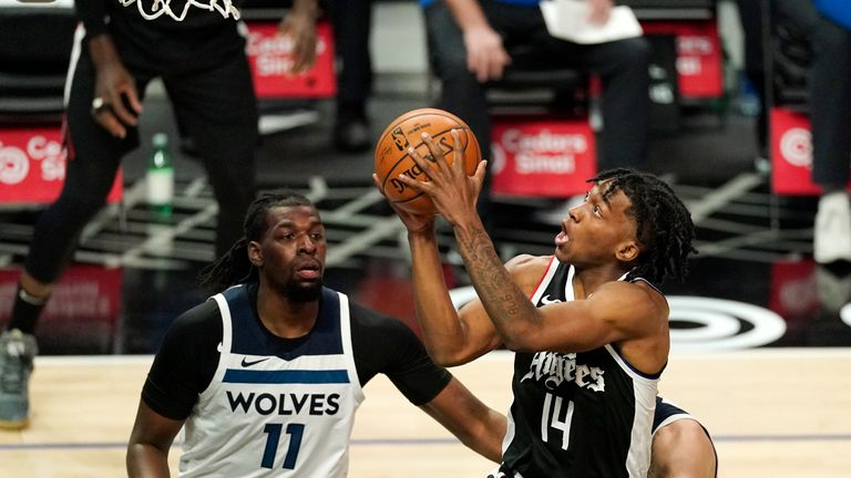 Los Angeles Clippers guard Terance Mann, right, shoots as Minnesota Timberwolves center Naz Reid defends during the first half of an NBA basketball game Sunday, April 18, 2021, in Los Angeles. (AP Photo/Mark J. Terrill)