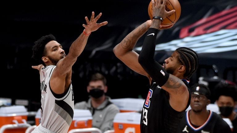 Los Angeles Clippers guard Paul George hits a shot over Portland Trail Blazers forward Derrick Jones Jr., left, during the second half of an NBA basketball game in Portland, Ore., Tuesday, April 20, 2021. The Clippers won 113-112.