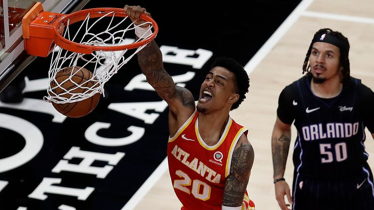 Atlanta Hawks' John Collins (20) scores as Orlando Magic guard Cole Anthony (50) watches during the second half of an NBA basketball game Tuesday, April 20, 2021, in Atlanta.