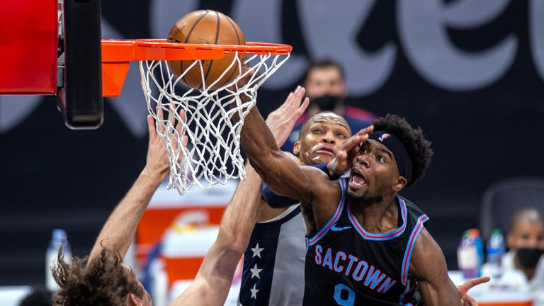 Sacramento Kings forward Terence Davis (9) dunks against Washington Wizards center Robin Lopez, left, and guard Russell Westbrook (4) during the fourth quarter of an NBA basketball game in Sacramento, Calif., Wednesday, April 14, 2021. (AP Photo/Hector Amezcua)