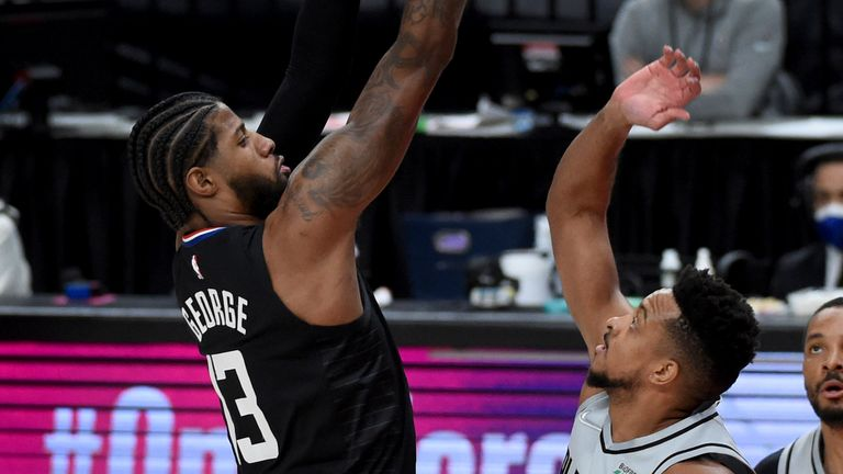 Los Angeles Clippers guard Paul George, left, hits a shot over Portland Trail Blazers guard CJ McCollum, right, during the first half of an NBA basketball game in Portland, Ore., Tuesday, April 20, 2021.