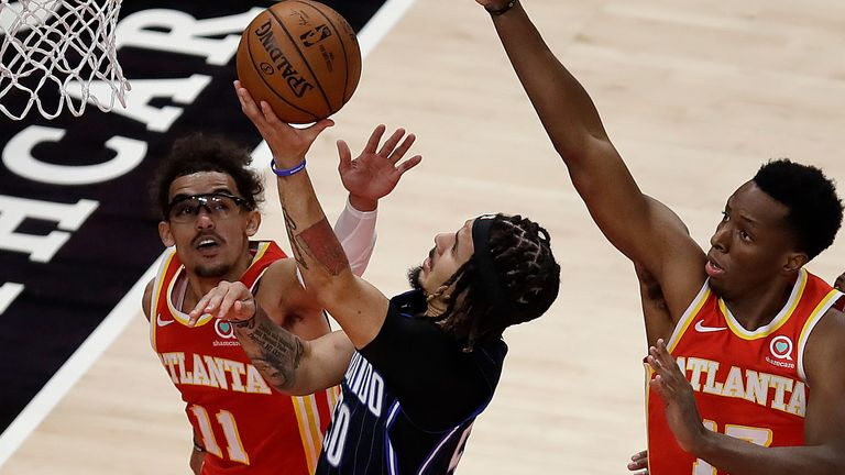 Orlando Magic guard Cole Anthony, center, shoots against Atlanta Hawks' Trae Young (11) and Onyeka Okongwu (17) in the first half of an NBA basketball game Tuesday, April 20, 2021, in Atlanta.