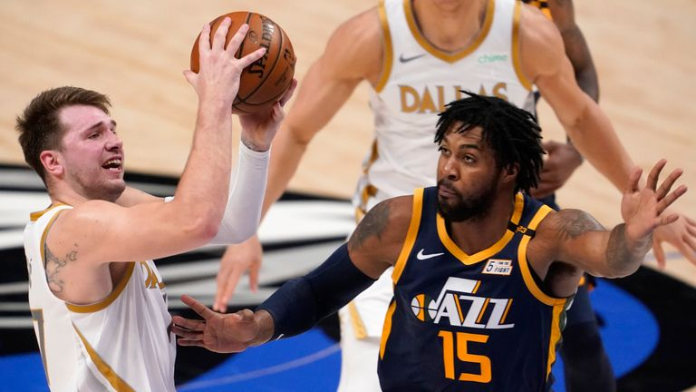 Dallas Mavericks guard Luka Doncic, left, takes a shot as Utah Jazz center Derrick Favors, right, defends in the second half of an NBA basketball game in Dallas, Monday, April 5, 2021.