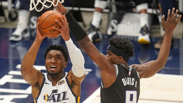 Utah Jazz guard Donovan Mitchell (45) goes to the basket as Sacramento Kings forward Terence Davis (9) defends in the first half during an NBA basketball game Saturday, April 10, 2021, in Salt Lake City.