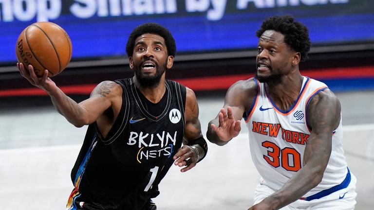 Brooklyn Nets' Kyrie Irving (11) drives past New York Knicks' Julius Randle (30) during the first half of an NBA basketball game Monday, April 5, 2021, in New York.